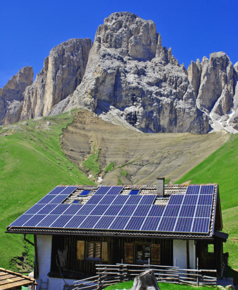 house roof with solar panels  background of the Dolomites mountains